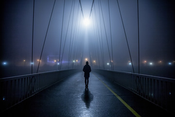 Lonely woman walking over bridge at night