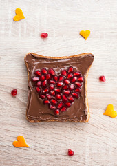 Chocolate sandwich with pomegranate heart - fun food idea for kids party or breakfast, Valentines day food background, top view, flat lay. Valentines day food decoration, closeup