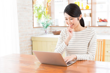 young asian woman using laptop in the dining