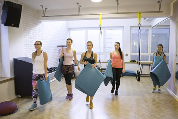 Group of women in class with exercise mats