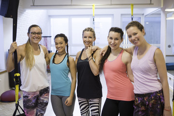 Happy women in exercise class standing side by side