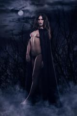 Beautiful gothic girl in a black cloak against a nightscape