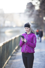Woman in sports clothes using MP3 player in city