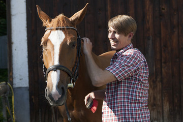Man on ranch brushing horse with groomer