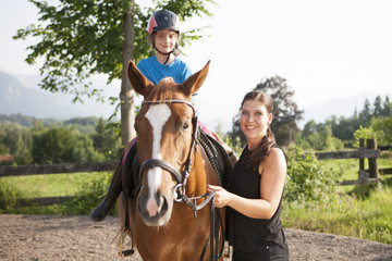 Girl learns to ride a horse with help of female instructor