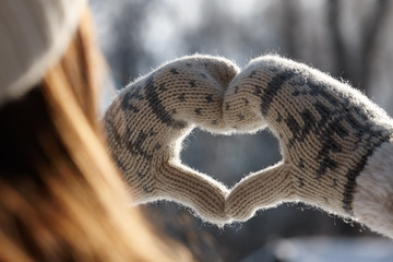 Woman holding hands in a heart shape
