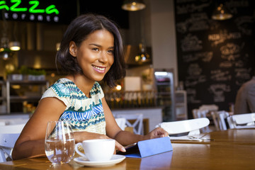 Mixed race woman sits in cafe using computer