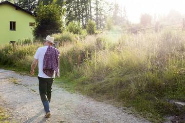 Senior farmer walking home in the evening