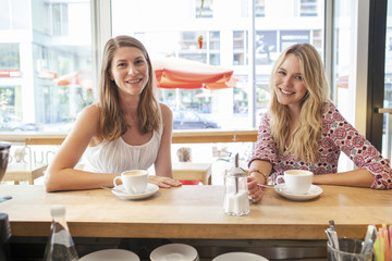 Two women have a cup of coffee in restaurant