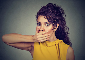 scared young woman covering with hand her mouth