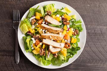 Orange Walnut Chicken Salad on a white plate with  dark wooden background top view