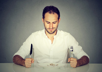 Man with fork and knife sitting at table looking at empty plate