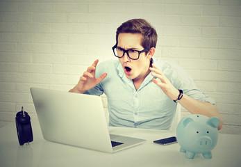 shocked man looking at laptop computer sitting at table