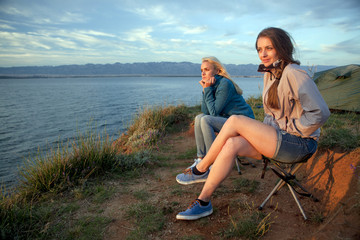Two women at campsite looking at sea
