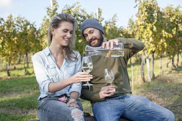 Couple drinking white wine on garden party in vineyard