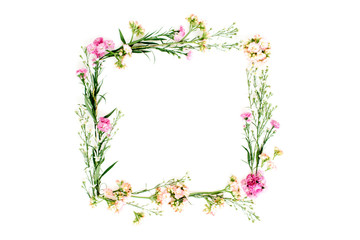 Wreath frame made of pink and beige wildflowers, green leaves, branches on white background. Flat lay, top view. Valentine's background