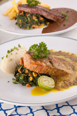 A decorating nice dish of salmon steak and beef served with mashed potato,lemon, saute spinach and sauce on background with wooden utensils.