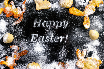 Cookies in the form of rabbits at Easter congratulation with powdered sugar on a dark background