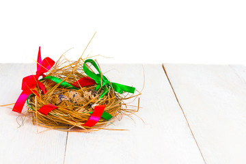 nest of straw and colorful ribbons with Easter eggs on a white wooden background