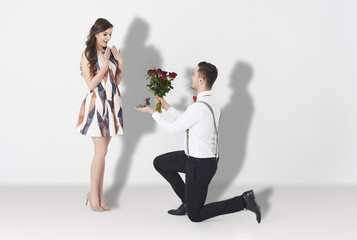 Young man surprising woman with engagement .
