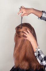 hairdresser coiffeur makes hairstyle fjr brown-haired person.