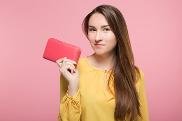 girl holding wallet next to her face over pink background isolated