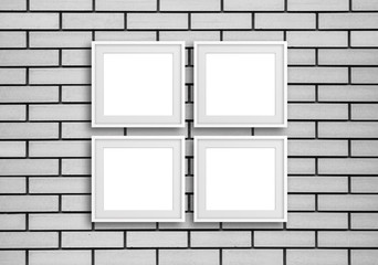 Group of  four white photo frames on grey bricks wall, gallery style design mock up