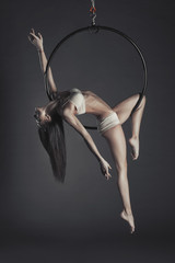 Young beautiful slim dancer on aerial hoop posing on a black studio background.