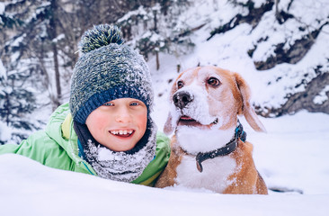 Boy with dog play in deep snow