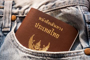 thailand passport in light denim jeans pocket - travel conept
