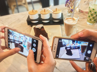 Close up people use smart phone to take picture of coffee cake before eat. Mobile photography