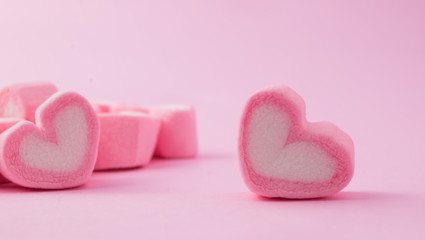Pink heart-shaped marshmallow in with pink background