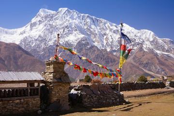 Nepalese village on Manang with buddhist stupa, praying flags and Mani wall, Annapurna III mountain summit on background, Annapurna Circuit Trek, Himalaya, Nepal, Asia. For horizontal postcard