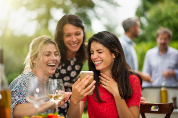 Group of female friends having fun while they watch photos
