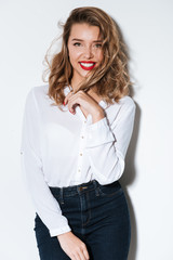 Portrait of a young smiling woman with red lipstick standing