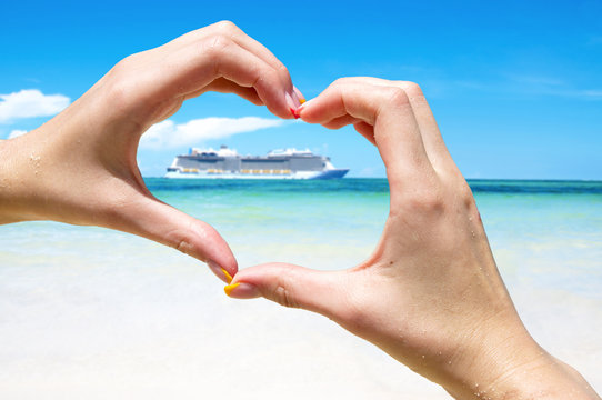 Cruise vacation concept. Cruise ship in the sea near the tropical island inside hands making heart shape. Tropical Resort. Vacation concept. Summer holidays. Tourism.