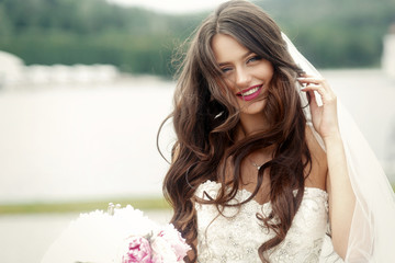 Stunning bride shakes her long curly hair and smiles tender