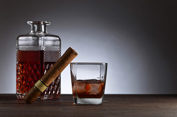 Glass of whiskey with cogar on a wooden table