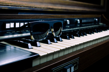 Vintage piano with a sunglasses over its keys
