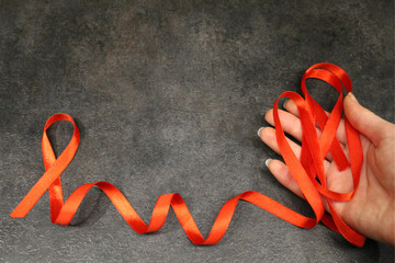 Red awareness ribbons in hand, isolated symbolic color logo concept lifting will campaign on health, public support for HIV STD cardiovascular disease