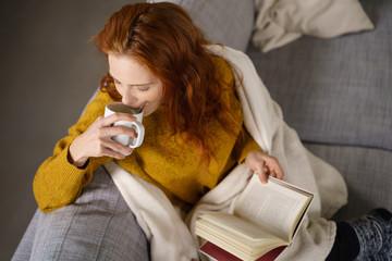 frau sitzt gemütlich mit einem buch und einer tasse tee auf dem sofa