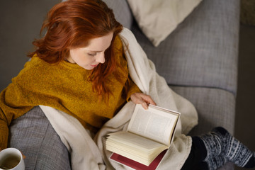 entspannte frau liest ein buch auf der couch