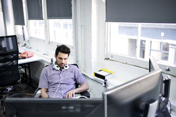 Caucasian businessman at his desk wearing headphones reading a book