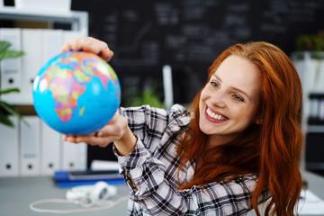 glückliche frau hält einen globus in den händen und lacht