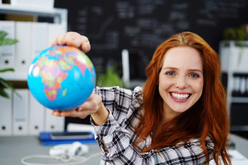 lachende frau zeigt einen globus