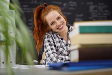 studentin sitzt am tisch mit einem stapel bücher