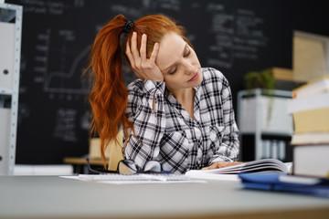 müde studentin stützt den kopf auf