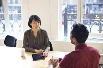 Asian businesswoman interviewing mixed race man in an office