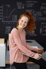 lachende junge frau im büro sitzt auf dem schreibtisch mit ihrem laptop