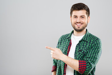 Man in green checked T-shirt pointing at something